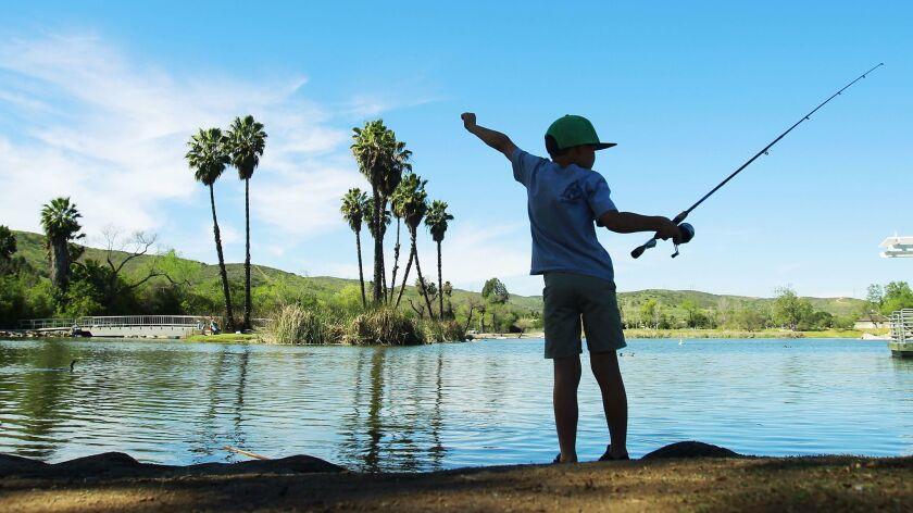 A child finds a shady place to fish on a hot afternoon at Santee Lakes Regional Park.