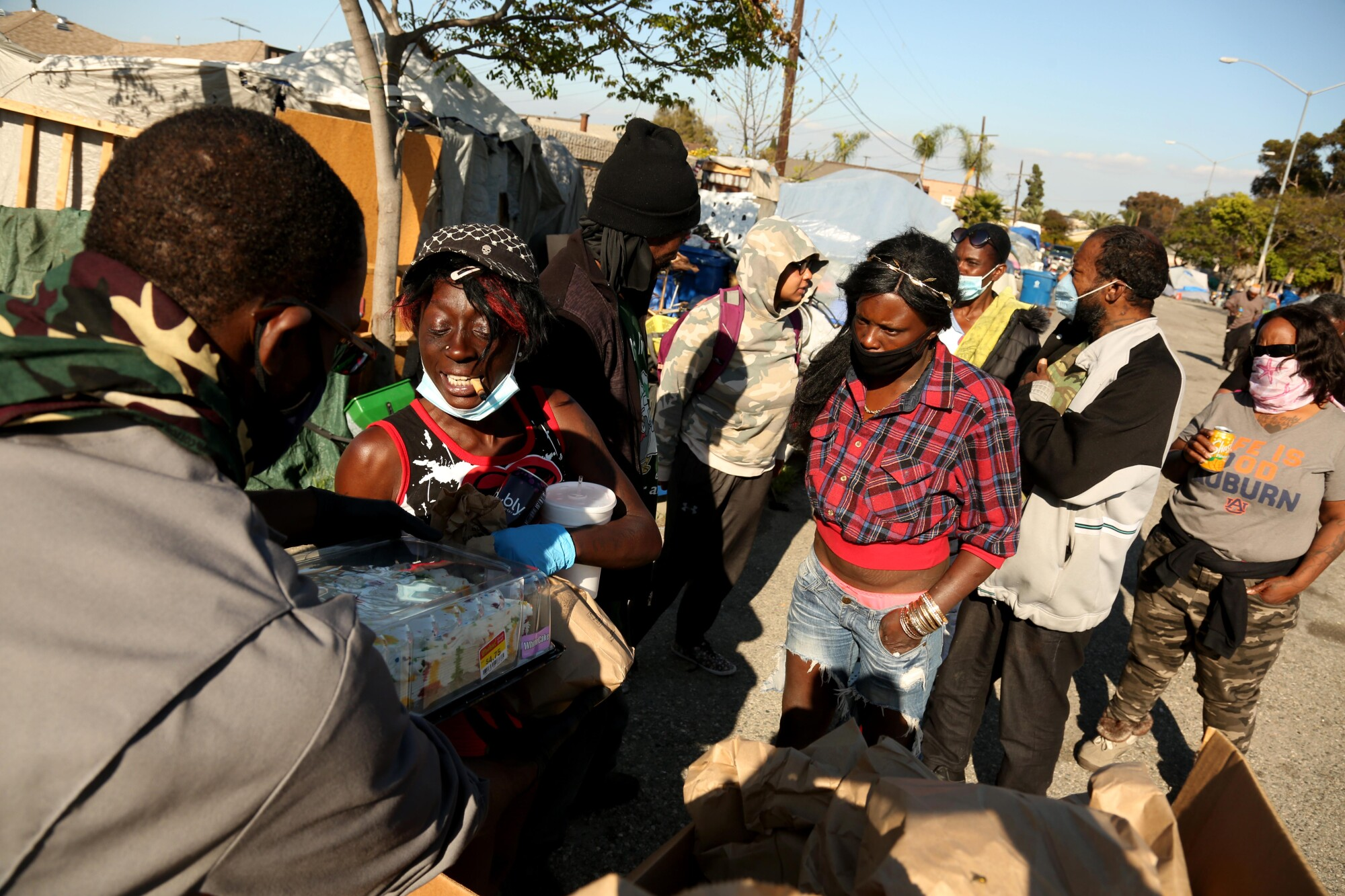 Gernay Quinnie Jr. meets with people living in a parking lot in South Los Angeles.