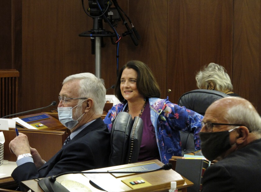 """FILE - In this May 18, 2020 file photo, Alaska state Sen. Lora Reinbold, center, is shown on the Senate floor in Juneau, Alaska. The nation's ongoing battle against the coronavirus is dividing lawmakers along partisan lines in state Capitols. Health screenings were required of legislative staff and media at the Alaska Capitol, though lawmakers could skip it. Protocols said masks were required. But Reinbold didn't wear one. """"It didn't make sense to me,"""" Reinbold said. """"I saw no research on cloth, silk, cotton face coverings ... that they prevent COVID."""" (AP Photo/Becky Bohrer, File)"""