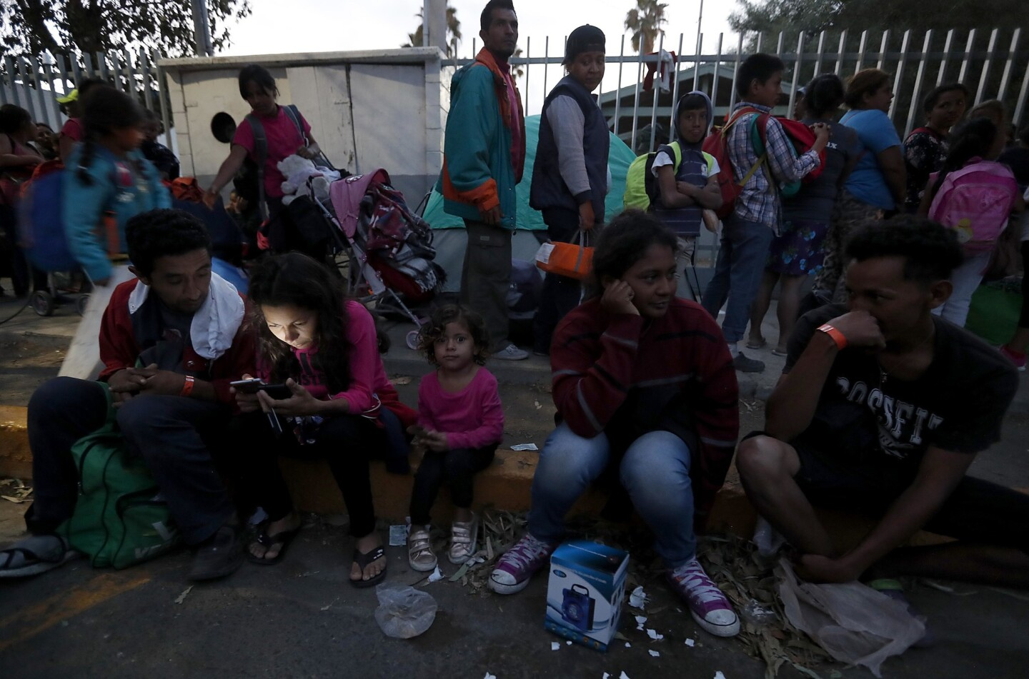 Migrants who are part of the caravan that has made its way from Honduras wait for shelter outside the Benito Juarez Sports Center in Tijuana on Nov. 15.