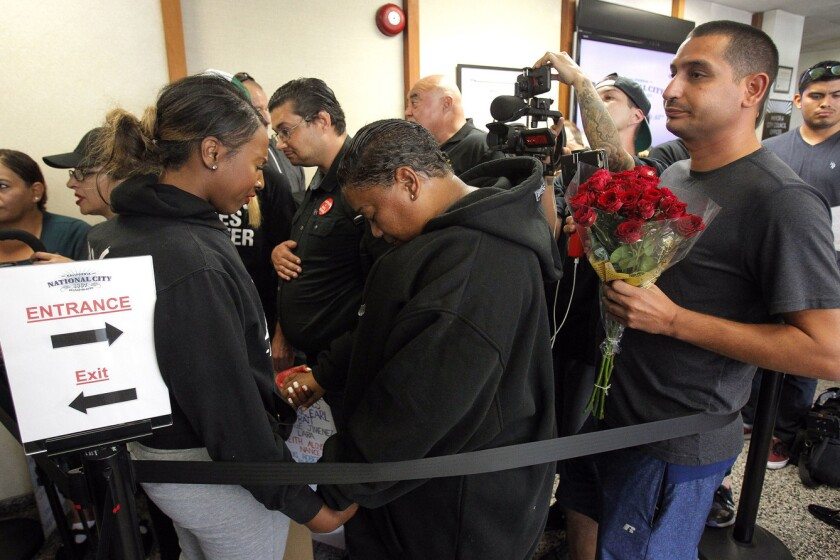 Aeiramique Blake, left, and Tasha Williamson hold hands as they pray in the lobby.