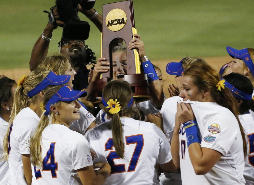 Florida pitcher Hannah Rogers holds the trophy as the team celebrates following an NCAA Women's College World Series softball tournament game against Alabama in Oklahoma City, Tuesday, June 3, 2014. Florida won the game 6-3 and took the title. (AP Photo/Sue Ogrocki)