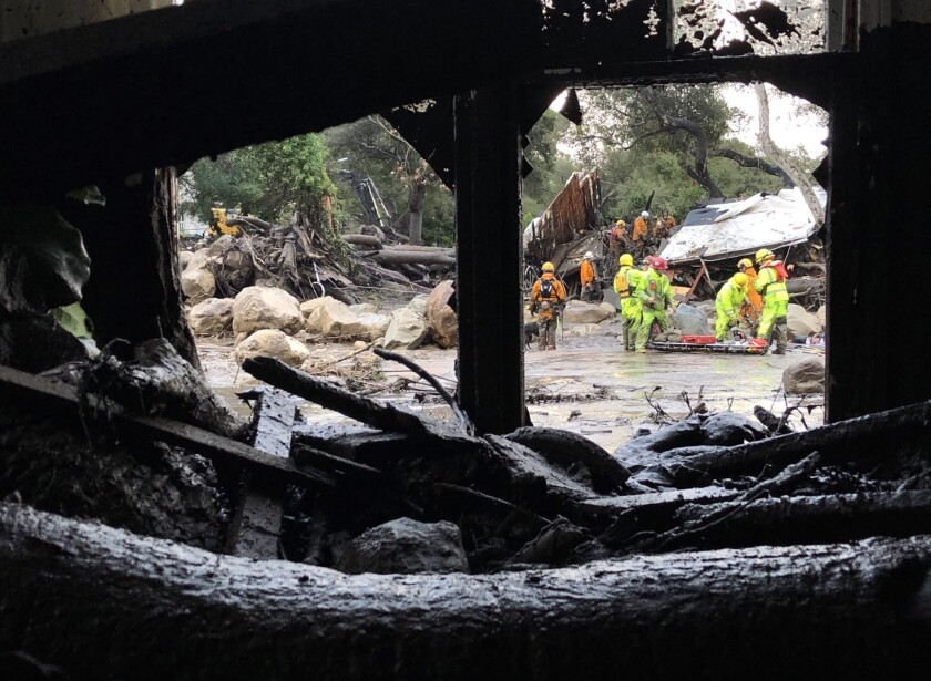 A swollen creek sent debris and mudflows racing along the 300 block of Hot Springs Road in Montecito following heavy rain Tuesday morning.