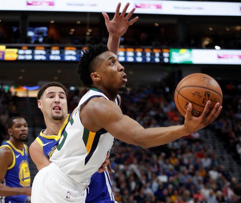 Donovan Mitchel (d) de Utah Jazz en acción ante Klay Thompson (i) de los Warrios, durante un partido de NBA que enfrenta a Utah Jazz y a Golden State Warriors hoy, martes 10 de abril de 2018, en el Energy Solutions Aren de la ciudad de Salt Lake City, en Utah (EE.UU.). EFE