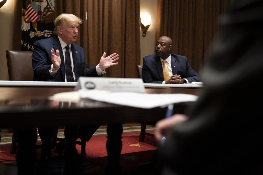 Sen. Tim Scott, R-S.C., right, listens as President Donald Trump speaks during a meeting on opportunity zones in the Cabinet Room of the White House, Monday, May 18, 2020, in Washington. (AP Photo/Evan Vucci)