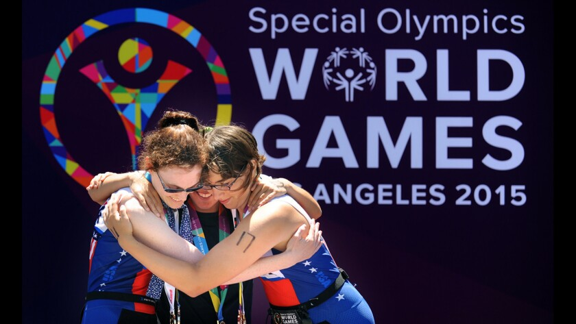 USA medal winners Amy Noctor, left, and Courtney Dreyfus, right hug gold medal winner Florencia Barranque after the triathlon competition of the Special Olympics in Long Beach on Sunday.