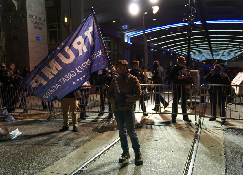 A supporter waves a Trump flag Thursday outside the Pennsylvania Convention Center in Philadelphia as votes are counted.