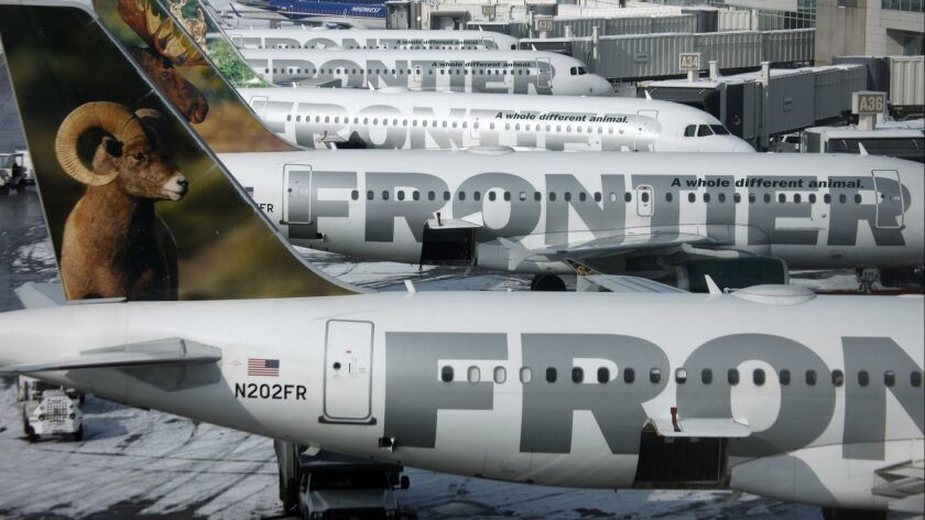 Frontier Airlines jetliners sit stacked up at gates at Denver International Airport in a 2010 file photo. Flight attendants on the carrier can now keep the tips they earn when passengers order food or drinks.