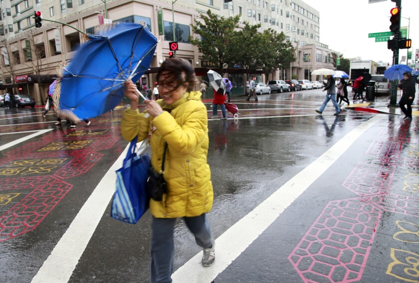 Pedestrians in Oakland's Chinatown battle the wind and rain as they cross at Franklin and 9th Street