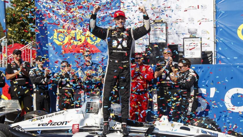 Simon Pagenaud, center, of France, celebrates in the Winner's Circle after taking first place at the