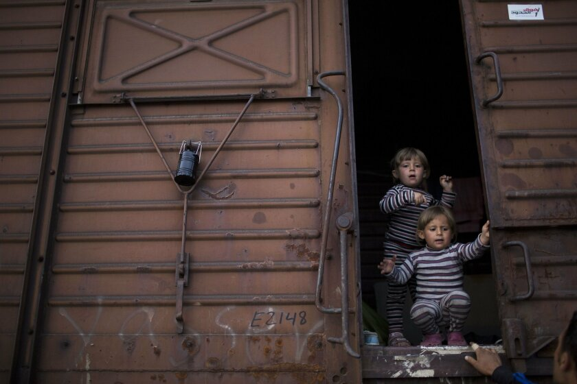FILE - In this Tuesday, May 10, 2016 file photo two Syrian twin sisters chat with a relative as they stand inside a freight car that their family live in the sprawling refugee and migrant tent city of Idomeni, on Greece's northern border with Macedonia. On government orders, Idomeni was cleared thi