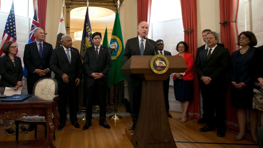 California Gov. Jerry Brown, center, discusses climate change at a news conference, Tuesday, June 13