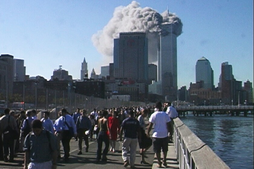 People walk alongside a river as the Twin Towers burn in front of them on Sept. 11, 2001.