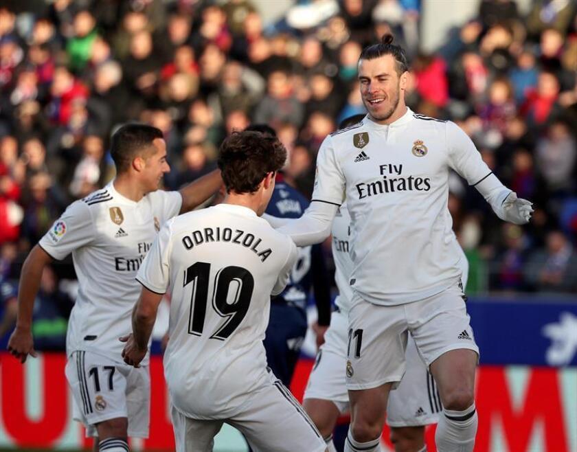 El delantero galés del Real Madrid Gareth Bale (d) celebra con sus compañeros, Odriozola y Lucas Vázquez (i) su gol ante el Huesca, durante el partido de la decimoquinta jornada de Liga en el estadio oscense de El Alcoraz. EFE