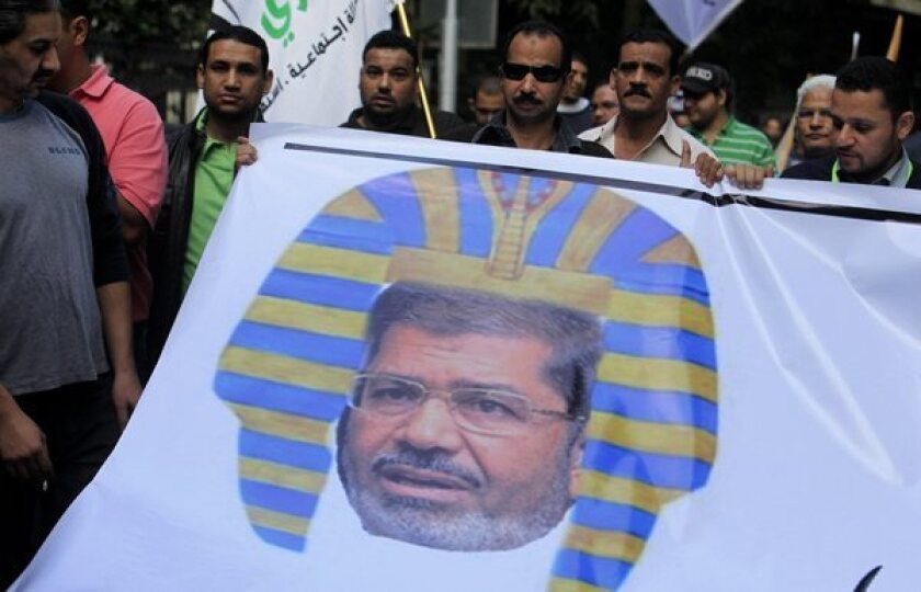 Egyptian protesters hold a banner depicting Egyptian President Morsi as a pharaoh in Cairo. Last week Morsi announced that his rule was immune to judicial oversight of any kind.