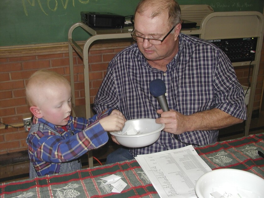 Eric Kuhlman, 3, left, helps master of ceremonies Stan Miller with Norcatur's annual Christmas Drawing