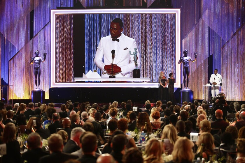 """Mahershala Ali won the trophy for male actor in a supporting role for """"Moonlight."""" He called for putting differences aside in his acceptance speech."""
