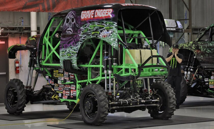 """Coty Saucier, far right, covers his ears as the Monster Truck """"Grave Digger"""" gets it's engine started Tuesday, Nov. 25, 2014, at Feld Entertainment in Ellenton, Fla. Feld Entertainment is trying to bring American-style Monster Truck entertainment to other parts of the world. (AP Photo/Chris O'Meara"""