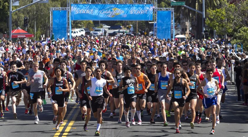 1,327 participants sprint down Grand Avenue at the start of the Men's and Women's 29 and under race during the Carlsbad 5000 on Sunday.