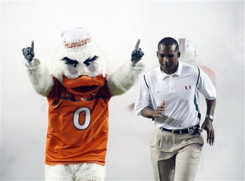 Miami head coach Randy Shannon runs alongside Miami's mascot, Sebastian the Ibis, before the start of an NCAA college football game against Oklahoma, Saturday, Oct. 3, 2009, in Miami. (AP Photo/J. Pat Carter)