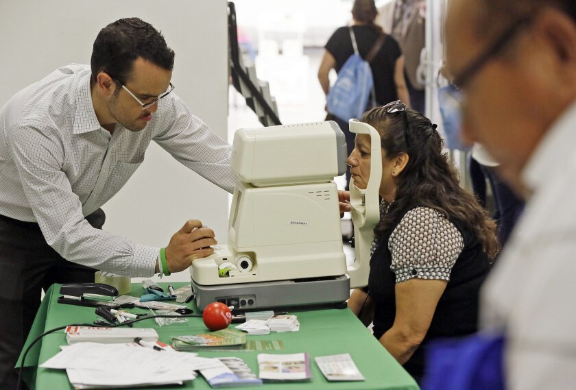 FILE - In this Oct. 1, 2013, file photo, Rosa Guerra, 52, right, gets a free eye exam during the Binational Health Week event held at the Mexican Consulate in Los Angeles. Health care advocates say President Obama's immigration action should enable hundreds of thousands of low-income immigrants in Calif., to qualify for Medi-Cal even as state officials say it's premature to comment. (AP Photo/Damian Dovarganes, File)