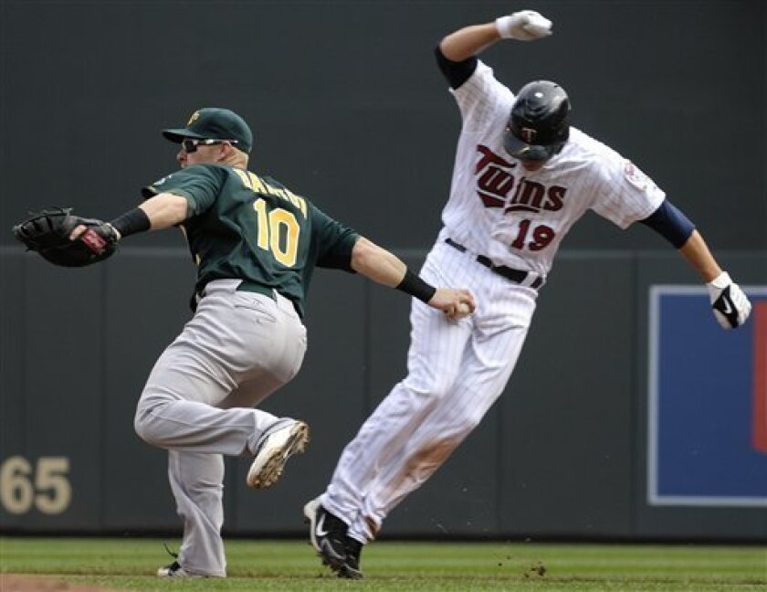Minnesota Twins' Danny Valencia, right, is tagged out in a rundown by Oakland Athletics' Daric Barton (10) while attempting to stretch a single into a double during the fifth inning of a baseball game Sunday, April 10, 2011, in Minneapolis. (AP Photo/Tom Olmscheid)