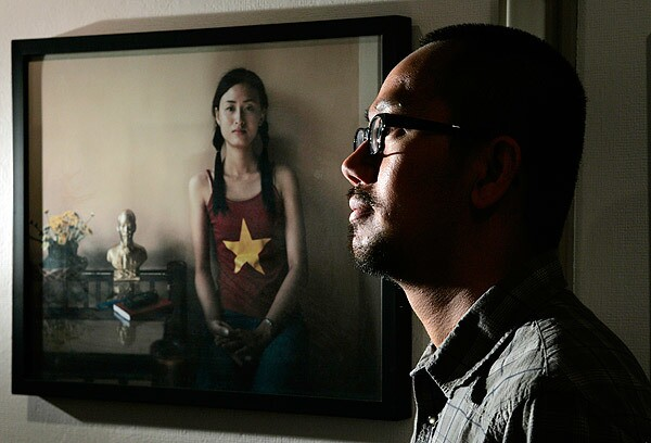 Brian Doan, a photographer, is facing the anger of Vietnamese Americans upset over his picture of a woman wearing a T-shirt with the Vietnamese flag and sitting next to a brass bust of former Communist leader Ho Chi Minh.