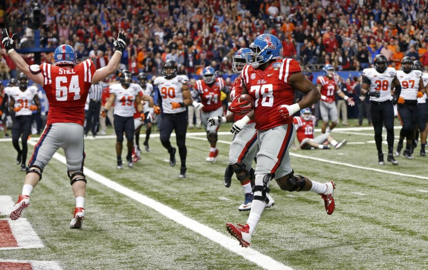 Mississippi offensive lineman Laremy Tunsil (78) carries for a touchdown in the first half of the Sugar Bowl college football game against Oklahoma State in New Orleans, Friday, Jan. 1, 2016. (AP Photo/Bill Feig)