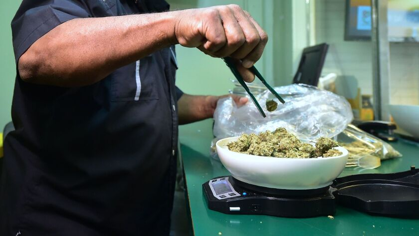 Marijuana is weighed on a scale at a Los Angeles dispensary subject to state regulations. On Monday, Irvine-based Weedmaps.com pushed back against the Bureau of Cannabis Control