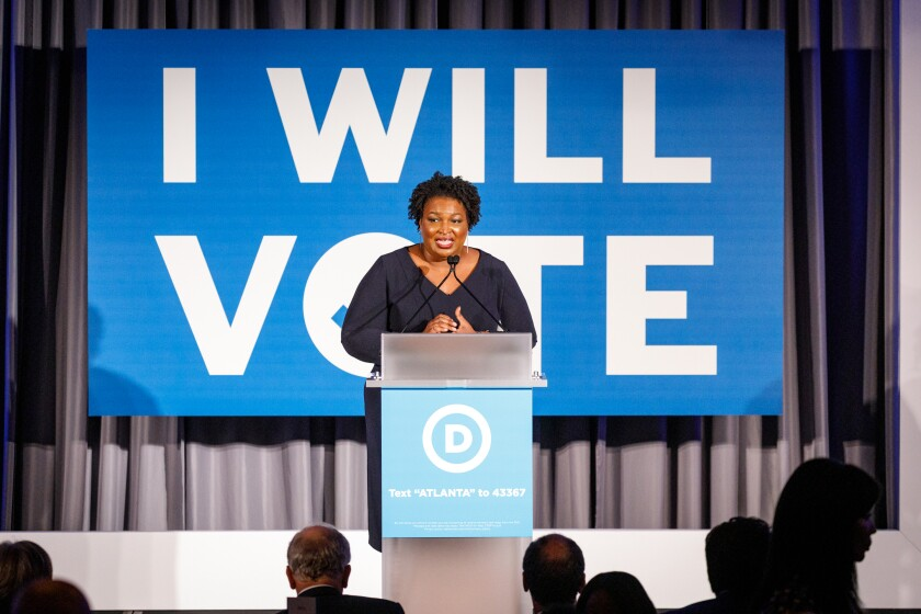 Stacey Abrams, behind a podium, speaks to a crowd at a Democratic National Committee event.