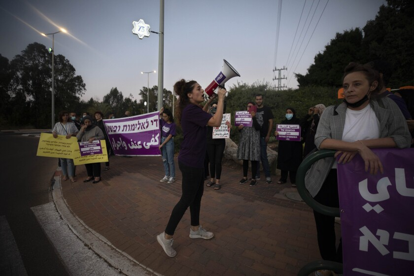 """Protesters hold signs and chant slogans during a demonstration against violence near the house of Public Security Minister Omer Barlev in the central Israeli town of Kokhav Ya'ir, Saturday, Sept. 25, 2021. Arab citizens of Israel are seeking to raise awareness about the spiraling rate of violent crime in their communities under the hashtag """"Arab lives matter,"""" but unlike a similar campaign in the United States, they are calling for more policing, not less. (AP Photo/Sebastian Scheiner)"""