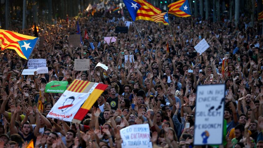 Demonstrators shake their hands as a sign of peaceful protest as they march in downtown Barcelona, Spain, on Oct. 3, 2017.