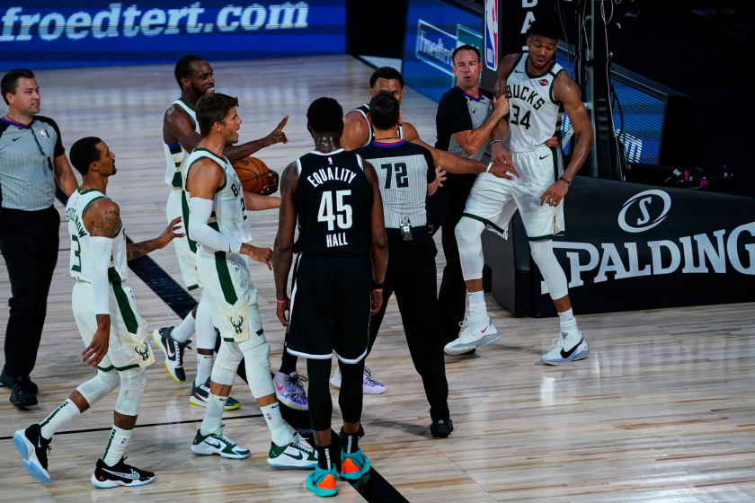 Referees separate players from the Milwaukee Bucks and Brooklyn Nets after a scuffle.