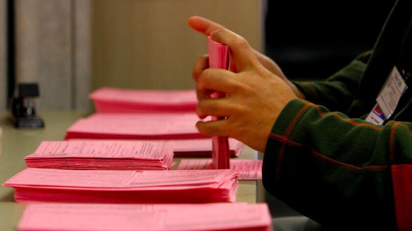 Un trabajador con sobres provisionales y seriados, en las Oficinas del Registro Electoral del Condado, en Norwalk, el 20 de noviembre de 2012 (Francine Orr/ Los Angeles Times).
