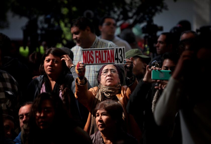 """A woman's banner reads """"We Are Missing 43!"""" at a presentation in Mexico City on Sunday to relatives of 43 missing Mexican college students from a school in Ayotzinapa."""