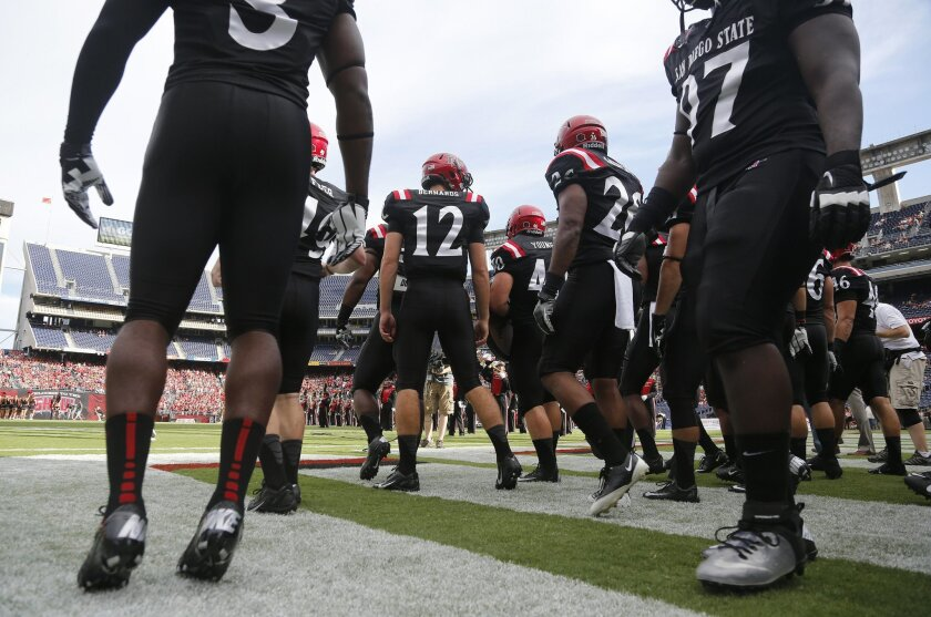 In this file photo, the Aztecs football team makes its entrance onto the field during SDSU's game against Eastern Illinois at Qualcomm Stadium.