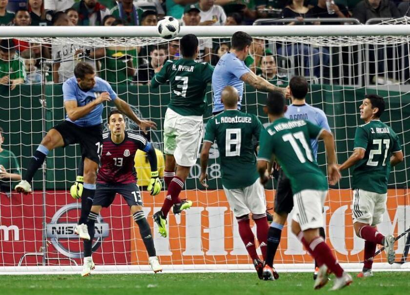 El portero de México, Guillermo Ochoa (c-i) trata de mantener el balón contra los jugadores de Uruguay en la segunda mitad del partido amistoso de fútbol entre México y Uruguay en el NRG Stadium en Houston. EFE