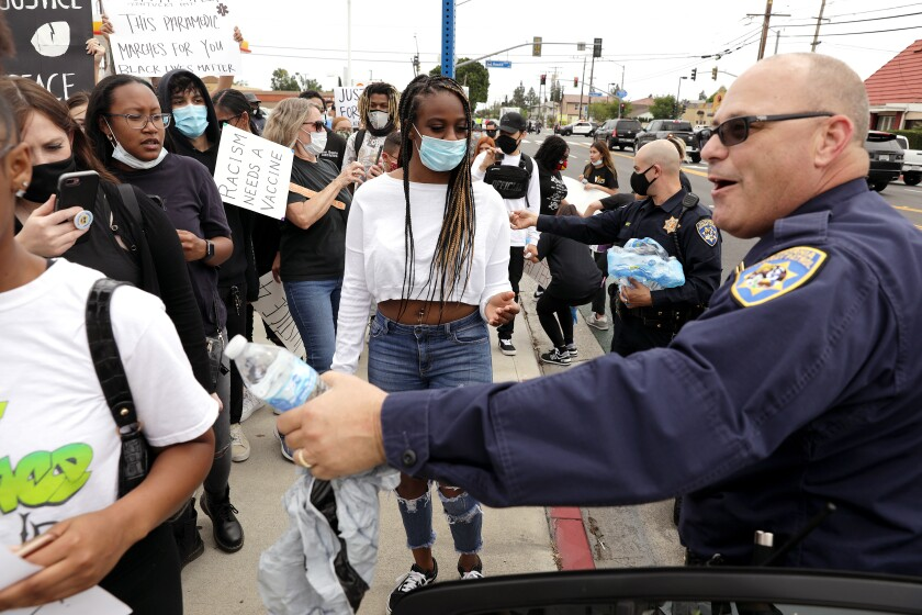 California Highway Patrol Captain of the Santa Fe Springs station, David Moeller, right, hands out water to demonstrators during a peaceful protest in Cerritos.