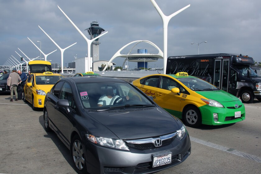 A car with Uber and Lyft stickers on its windshield leaves the departure terminal at Los Angeles International Airport.