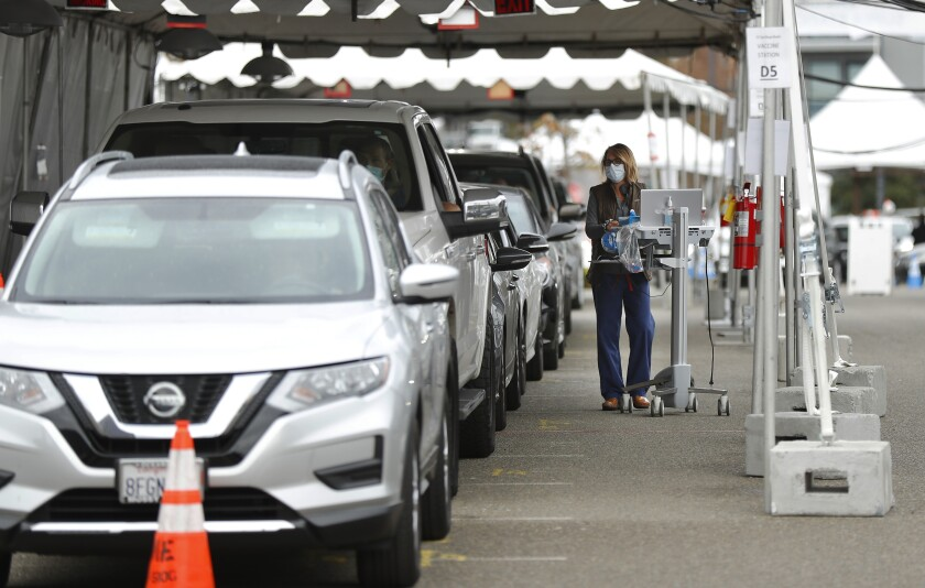 People wait in their cars after getting a COVID-19 vaccine shot at the Petco Park Vaccination Super Station