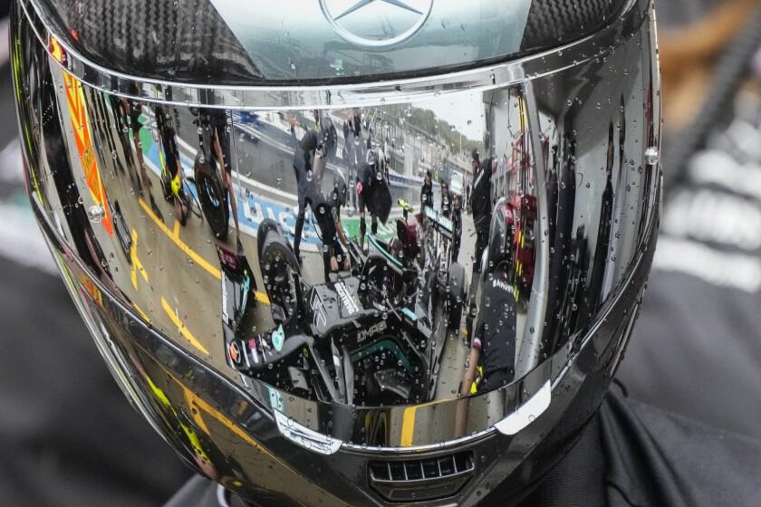 Personal técnico de Mercedes aparece reflejado en un casco mientras trabaja en el auto del piloto finlandés Valtteri Bottas, en el garaje de la escudería en el Autódromo de Sochi, Rusia, el jueves 23 de septiembre de 2021. (AP Foto/Sergei Grits)