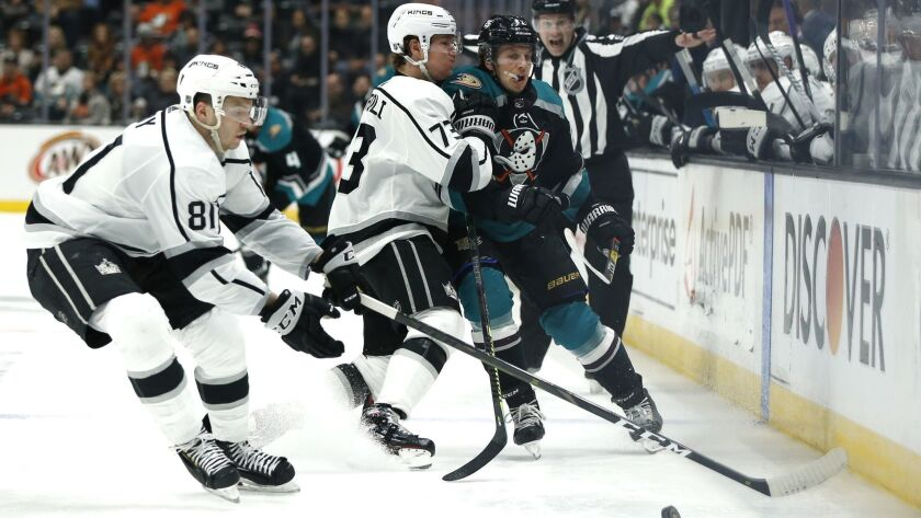 The Kings' Tyler Toffoli, center, and the Ducks' Rickard Rakell fight for control of the puck as L.A.'s Matt Roy moves in during a March 10 game at Honda Center.
