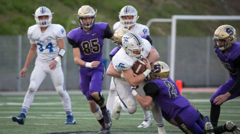 La Jolla Country Day quarterback Braxton Burmeister tries to escape Santana tackler Cameron Kane.