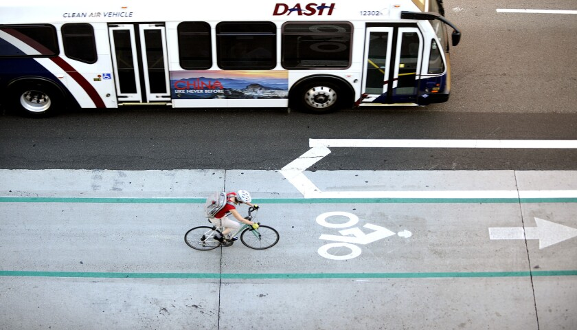 A cyclist using a bike lane travels alongside a city bus in downtown Los Angeles on Aug. 11.
