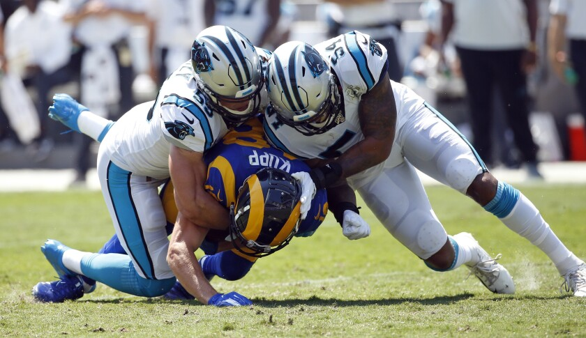 Rams wide receiver Cooper Kupp, bottom, is tackled by Carolina Panthers linebackers Luke Kuechly, left, and Shaq Thompson.