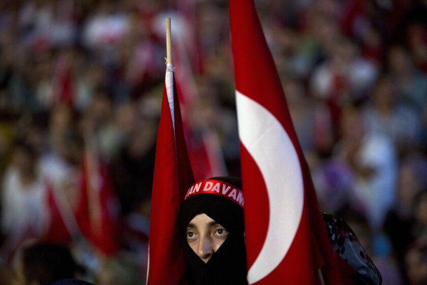 A woman takes part in a pro-government rally in Taksim Square, Istanbul, Tuesday, July 19, 2016. The Turkish government accelerated its crackdown on alleged plotters of the failed coup against President Recep Tayyip Erdogan. The rebellion, which saw warplanes firing on key government installations