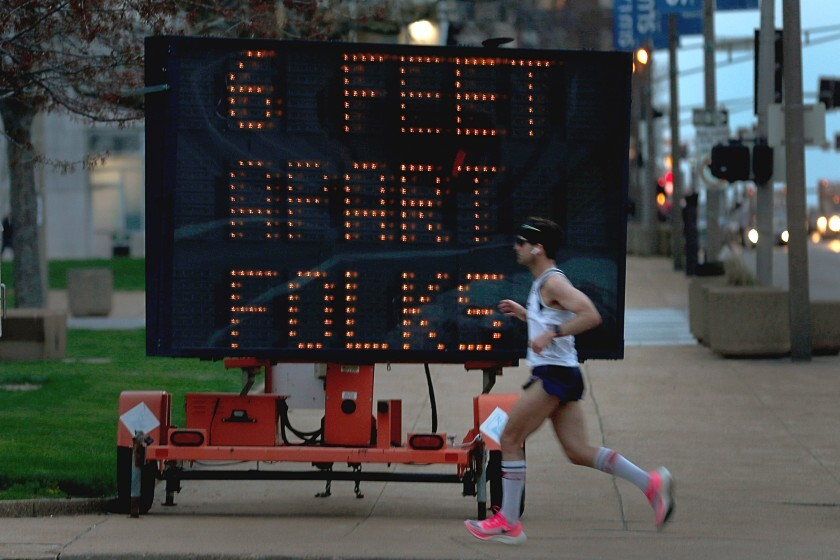 "A jogger runs before a lighted sign that says ""6 feet apart folks."""