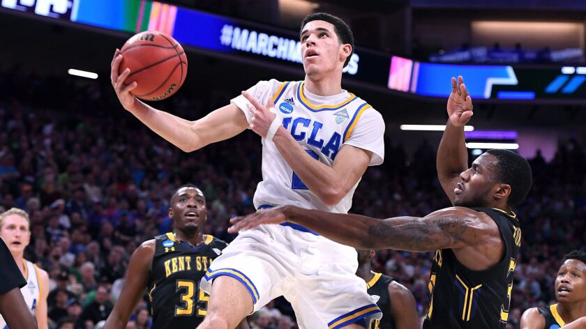 UCLA guard Lonzo Ball scores as he's fouled by Kent State forward Kevin Zabo during the first half Friday night.
