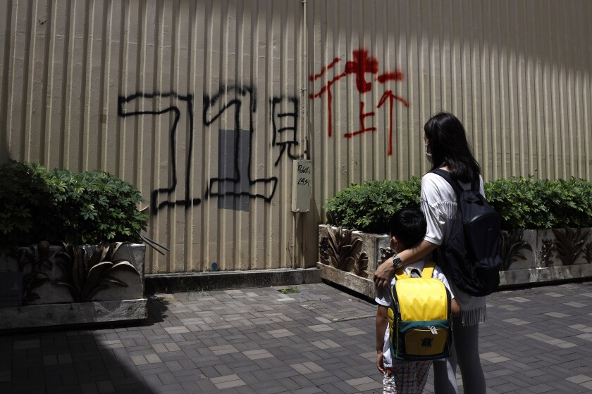 """Pamela Lam and her son stand in Hong Kong, Friday, July 3, 2020. Lam's 6-year-old son fell in love with the Hong Kong protest anthem, """"Glory to Hong Kong,"""" the first time he heard it and sings it quite often. The Chinese painted on wall reads: """"See you on street at July 1."""" Lam agreed to be photographed only if her face was not shown, fearing possible retribution from authorities. (AP Photo/Kin Cheung)"""