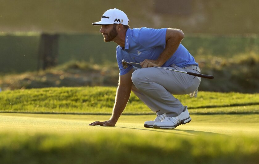 Dustin Johnson lines up his putt on the seventh hole during the rain delayed second round of the U.S. Open golf championship at Oakmont Country Club on Friday, June 17, 2016, in Oakmont, Pa. (AP Photo/Charlie Riedel)